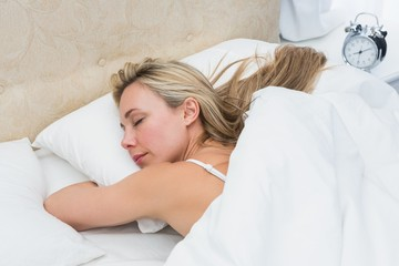 Pretty blonde sleeping in bed with alarm clock
