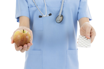 Nurse or doctor showing a pack of tablets and an apple