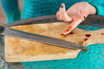 closeup of injured finger bleeding from a knife cut