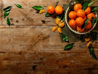 Basket with tasty tangerines on a wooden table