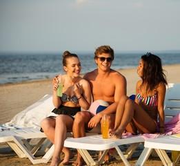 Friends sunbathing on a deck chairs on a beach