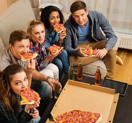 Friends with pizza and bottles of drinks having party