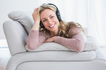 Smiling blonde lying on couch listening music