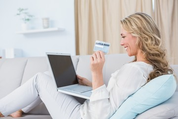 Happy blonde sitting on couch shopping online