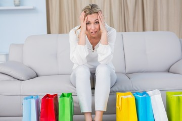 Blonde sitting on couch getting headache near shopping bags