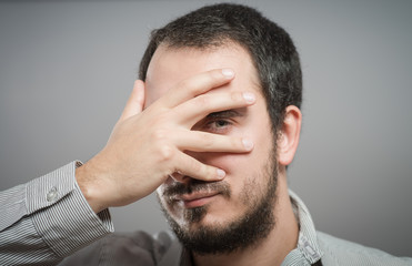 Portrait of a handsome man covering his eyes with hand