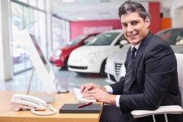 Smiling businessman typing on laptop