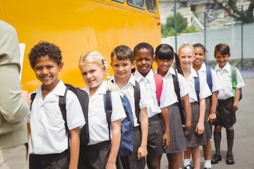 Cute schoolchildren waiting to get on school bus