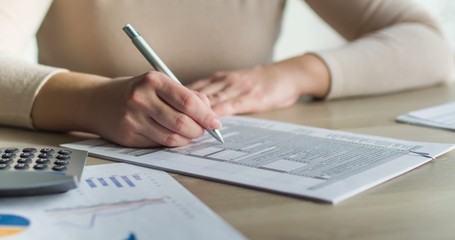 Woman filling tax form, calculating expenses