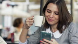 Young, pretty businesswoman using smartphone, drinking coffee