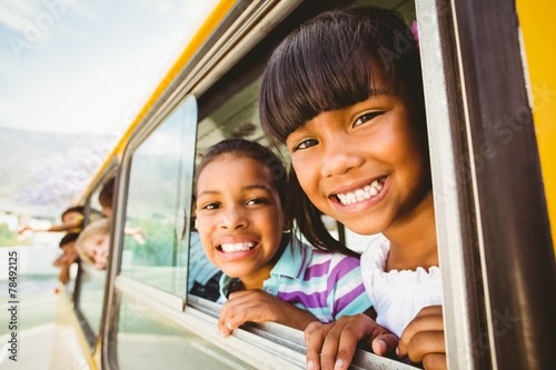 Cute pupils smiling at camera in the school bus - 78492125