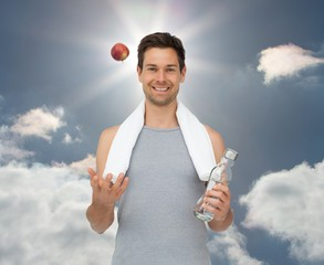CSmiling fit young man with apple and water bottle