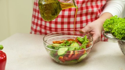 Woman Pouring Olive Oil Onto Vegetables Salad