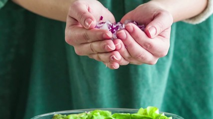 Adding sliced red onion to salad