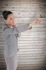 Unsmiling thinking asian businesswoman pointing