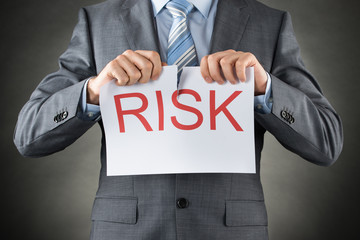 Businessman Tearing The Word Risk On Paper