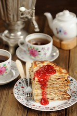 Russian bliny with raspberry jam, vintage samovar and teaware