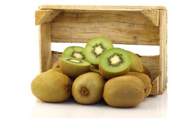 green kiwi fruit in a wooden box on a white background
