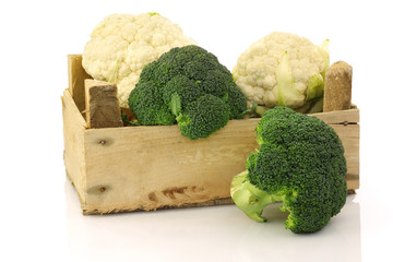 cauliflower and broccoli in a wooden crate on a white background