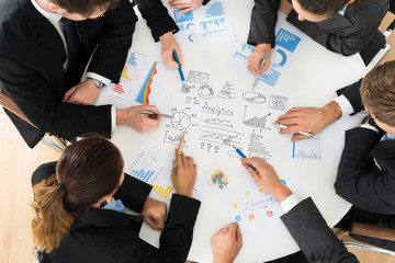 Group Of Businesspeople Analyzing Graph