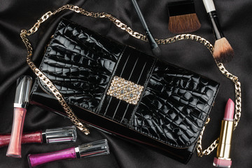 Beautiful bag from patent leather and cosmetics lying on black s