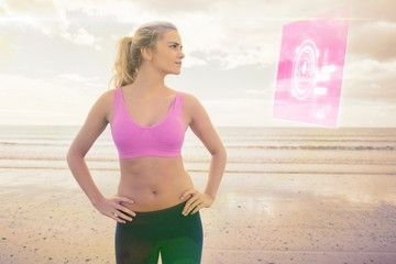 Composite image of toned woman with hands on hips on beach