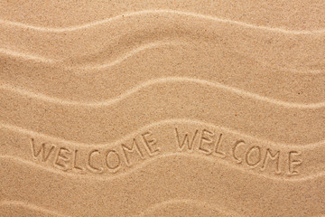 Welcome inscription on the wavy sand