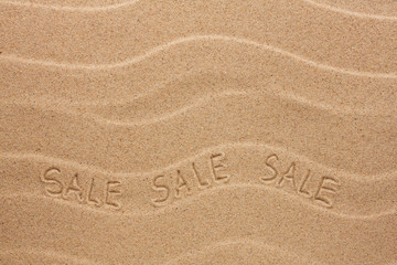 Sale inscription on the wavy sand