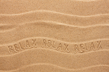 Relax inscription on the wavy sand