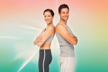 Portrait of a happy fit young couple with hands crossed