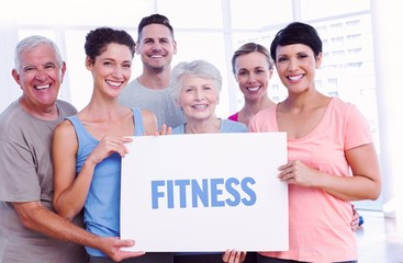 Fitness against fit people holding blank board in yoga class