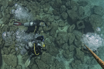 diver bubbles near boat rope underwater