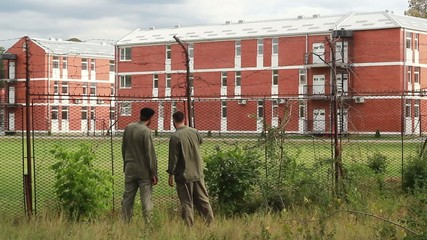 Prisoners in uniform in the jail backyard watching and talking