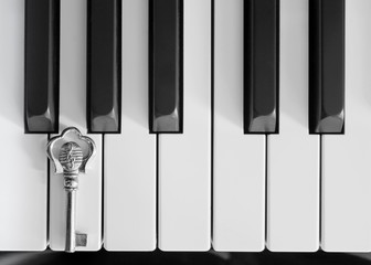 Piano keys and a silver key; black and white photo