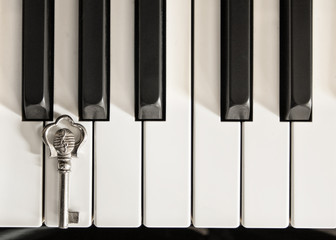Piano keys and a silver key with G-clef symbol