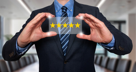 Businessman holding five star rating. Office Bakcground