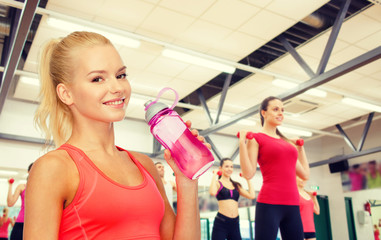 smiling sporty woman with water bottle