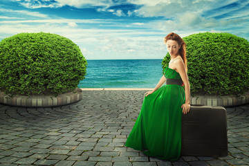 Beautiful woman in green dress sitting on a suitcase