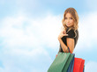 young happy woman with shopping bags over blue sky