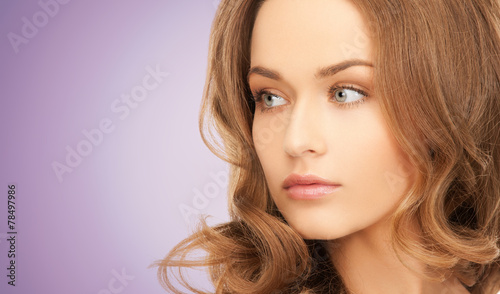 canvas print picture beautiful young woman face over violet background