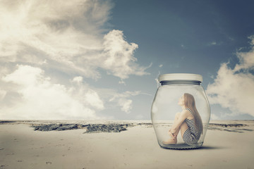 young woman sitting in jar in desert. Loneliness outlier concept