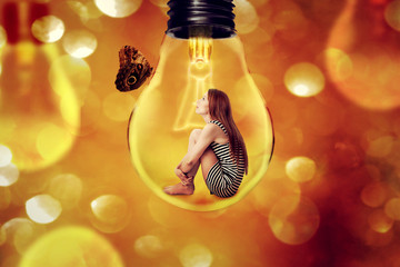 Lonely woman sitting inside light bulb looking at butterfly