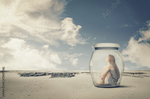 young woman sitting in jar in desert. Loneliness outlier concept - 78498146
