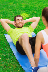 smiling man doing exercises on mat outdoors