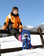child with blue snowshoes in the mountains in winter