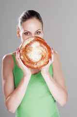 Attractive girl looks out behind a round bun, over gray backgrou