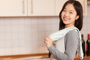Asian smiling woman standing in the kitchen