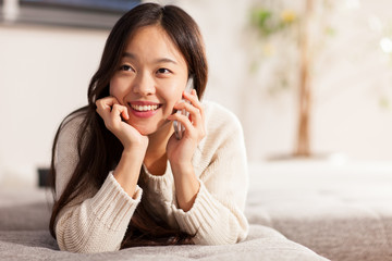Asian woman is smiling while phoning