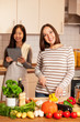 Two smiling female friends are cooking together at home