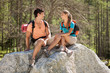 Young couple is relaxing on a big rock in the mountains